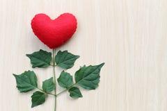 在一张木桌安置的红色心脏连接用t分支  库存图片