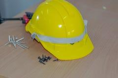 在一张木桌安置的黄色安全帽子发行螺丝 库存图片