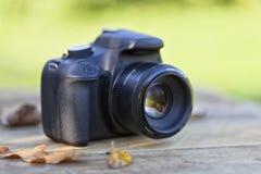 在一张木桌顶部的一台数字照相机与一些下落的事假 库存图片