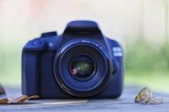 在一张木桌顶部的一台数字照相机与一些下落的事假 库存照片
