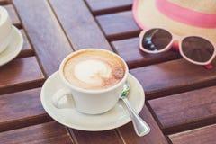 在一张木棕色桌上是有热奶咖啡的一个杯子,帽子,玻璃 夏天,咖啡馆,定调子葡萄酒的休息 免版税库存图片