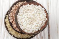 在一张木白色桌上的集合各种各样的有机未加工的米在陶瓷 免版税库存图片