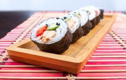 在一张木盛肉盘和竹子席子的寿司 库存图片