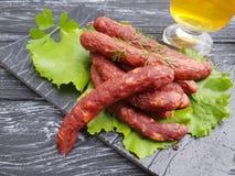 在一张木背景莴苣桌上的香肠啤酒沙拉叶子猪肉板食物开胃菜有机晚餐食家厨房 免版税库存图片