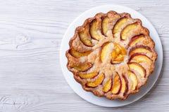 在一张木背景顶视图的圆的桃子饼 免版税库存照片