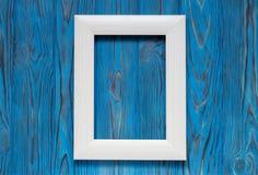 在一张木蓝色桌上的白色垂直的照片框架 库存照片