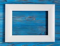 在一张木蓝色桌上的白色水平的照片框架 免版税库存图片