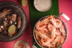 在一张桃红色桌、玻璃用白葡萄酒和调味汁上的虾 库存图片