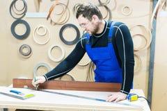 在一张桌上的一位有胡子的疲乏的英俊的木匠与铅笔画在委员会的一个标志 在工作场所有  库存照片