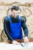 在一张桌上的一位有胡子的疲乏的英俊的木匠与铅笔画在委员会的一个标志 在工作场所有  图库摄影