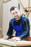 在一张桌上的一位有胡子的疲乏的英俊的木匠与铅笔画在委员会的一个标志 在工作场所有  免版税库存照片