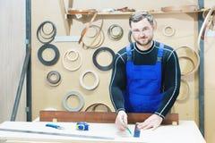 在一张桌上的一位有胡子的疲乏的英俊的木匠与铅笔画在委员会的一个标志 在工作场所有  库存图片