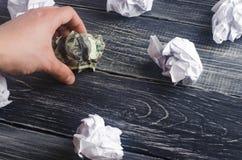 在一张桌上的一被弄皱的美元在白皮书球旁边 认为和发现新的企业想法的过程,有益 库存照片