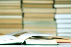 在一张桌上的几本开放书在一许多被堆积的书前面 免版税库存照片