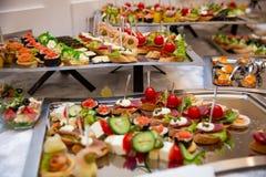在一张桌上的承办的桌集合服务各种各样的快餐在宴会 套冷的快餐,点心,饮料,特写镜头 侧视图 图库摄影