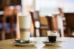 在一张桌上的拿铁和浓咖啡杯子在caffe 免版税库存照片