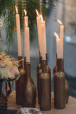 在一张桌上的灼烧的蜡烛在从瓶的烛台 免版税库存图片