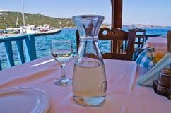 在一张桌上的白葡萄酒在少许由海的一典型的希腊taverna 图库摄影