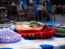 在一张桌上的羊毛内衣的童帽与人在背景中 库存图片
