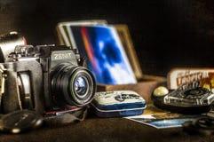 在一张桌上的老照相机与图片和老光度计 库存图片