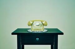 在一张桌上的老轮循拨号电话,与一个减速火箭的作用 免版税库存照片