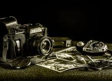 在一张桌上的老b/w照相机与图片和老光度计 免版税库存照片