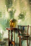 在一张桌上的花瓶在与绿色墙壁的一把椅子旁边 背景 库存照片