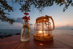 在一张桌上的蜡烛在日落在酸值Kood海岛上的视图餐馆 免版税库存照片