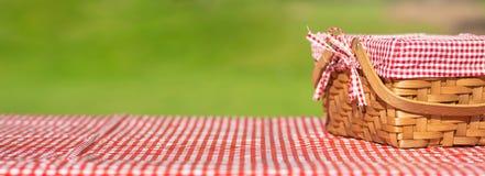 在一张桌上的野餐篮子与一张红色桌布 r ?? ?? 免版税库存照片