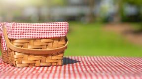 在一张桌上的野餐篮子与一张红色桌布 r ?? ?? 库存照片
