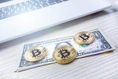 在一张桌上的Bitcoin金黄硬币与美元钞票和膝上型计算机 虚拟的货币 Cryptocurrency事务 办公室背景 库存图片