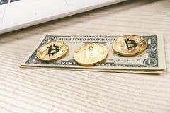在一张桌上的Bitcoin金黄硬币与美元钞票和膝上型计算机 虚拟的货币 Cryptocurrency事务 办公室背景 免版税库存照片