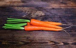 在一张棕色木桌上的三棵新鲜的橙色红萝卜 库存照片