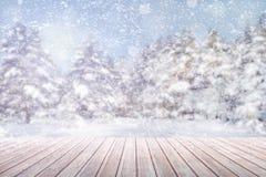 在一张棕色木桌上的看法反对迷离和降雪的一个冬天森林 免版税库存照片