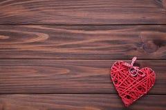 在一张棕色木桌上的红心 红色上升了 库存图片