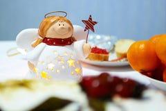 在一张欢乐桌上的圣诞节天使 免版税图库摄影