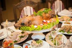在一张欢乐桌上的被烘烤的牛奶猪 库存照片