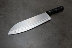 在一张深灰桌上的厨师刀子 库存照片