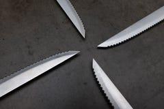在一张深灰桌上的被加锯齿的刀子 免版税库存照片