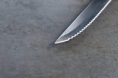 在一张深灰桌上的被加锯齿的刀子 免版税图库摄影