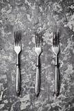 在一张灰色具体桌上的三把古色古香的叉子 顶视图 库存照片