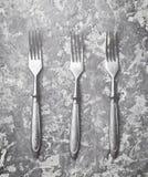 在一张灰色具体桌上的三把古色古香的叉子 顶视图 库存图片