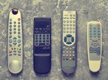 在一张灰色具体桌上的许多电视遥控 顶视图 库存照片