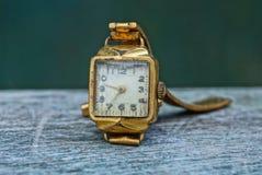 在一张灰色桌上的老破旧的黄色手表 库存照片
