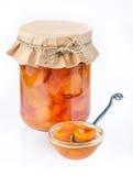 在一张瓶子封面纸的杏子果酱与匙子 图库摄影
