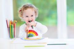 在一张白色书桌的滑稽的笑的女婴图画 免版税库存图片
