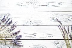 在一张白色土气木桌上的干淡紫色花 库存图片