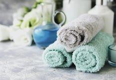 在一张白色大理石桌上的温泉集合与堆毛巾,选择聚焦 库存照片