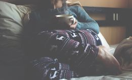 在一张白色床上的女孩与一杯咖啡 库存图片