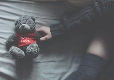 在一张白色床上的女孩与软的玩具 库存照片
